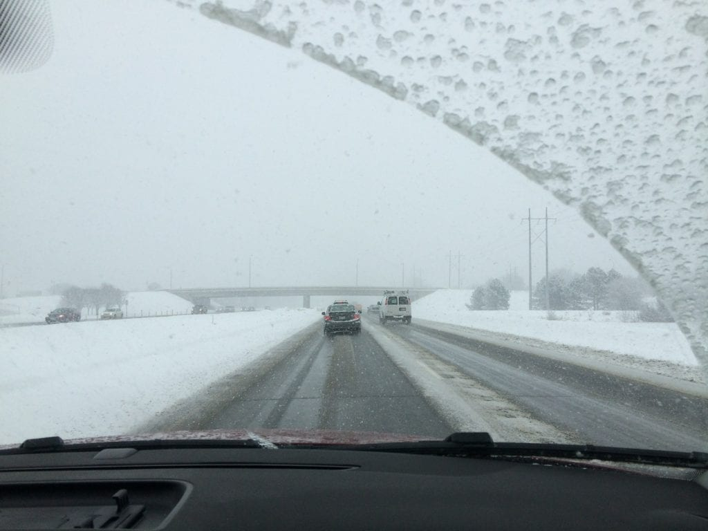 View from a front windshield on a winter road trip.