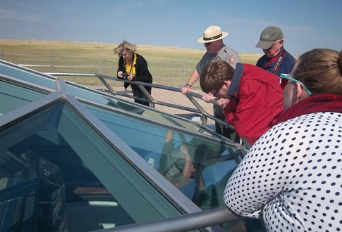 Visitors peer inside a decommissioned Minute Man Missile silo near Wall, South Dakota.