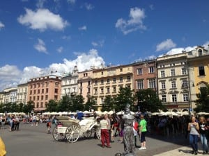 Krakow's main square is lined with sidewalk cafes and filled with vendors, walkers, performers