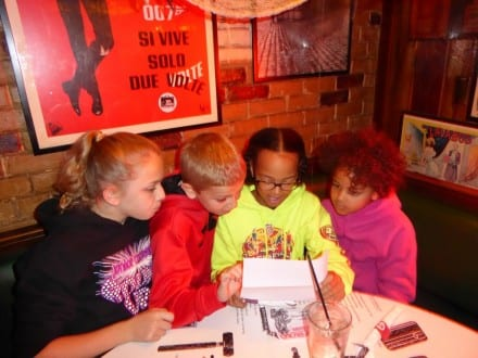 Photo by Jamie Bartosch/Suburban TravelingMom Kids review their mission while dining at Safe House, a spy-themed restaurant and museum in downtown Milwaukee.