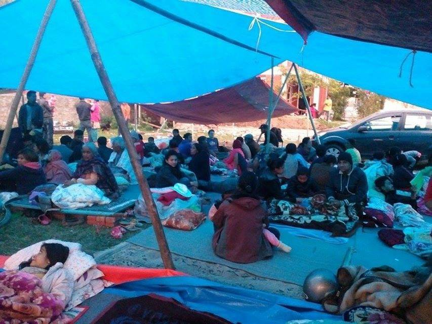 People huddle in makeshift tent shelters after the Nepal earthquake