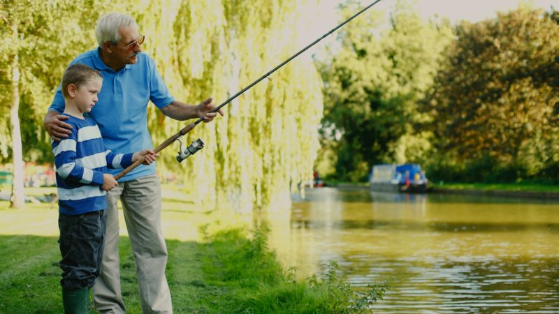 Grandfather fishing with grandson