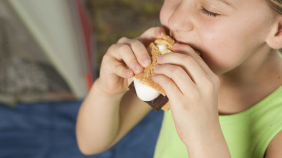 Girl eating s'mores on a camping trip.