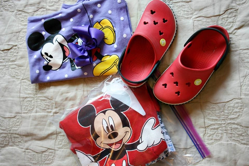 Disney outfits in zip close bags with child's red Crocs