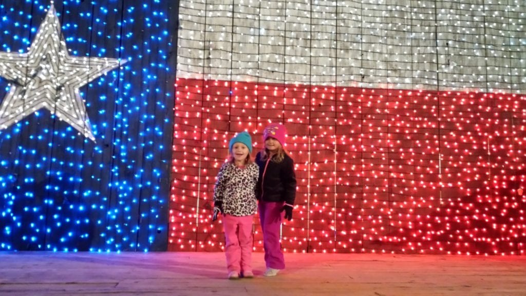 Two girls pose in front of the Texas flag light set up at Santa's Wonderland in Texas - TravelingMom