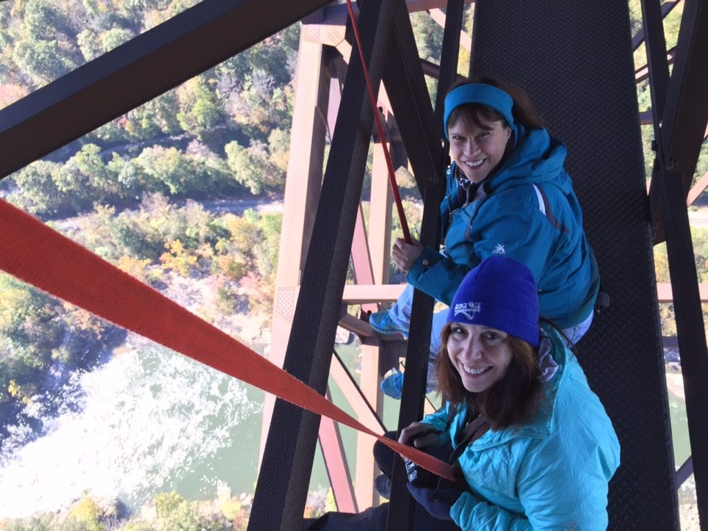 The daredevils dangle their feet over the edge of the New River Gorge Bridge (while still attached to their harnesses). Photo courtesy of Fran Capo/ Adventure