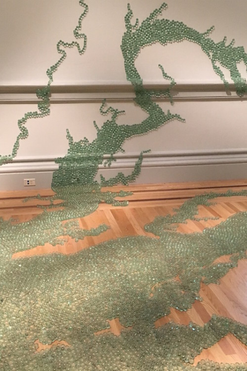 Maya Lin's art installation at the Renwick Gallery uses marbles to cover floors, walls and trail up to the ceiling, shaping rivers, fields and mountains.
