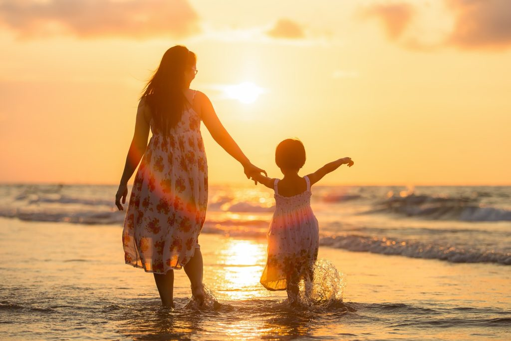 Mother and daughter at the beach at sunset.