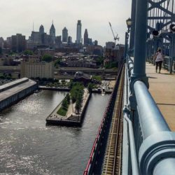 Pedestrian path on the Ben Franklin Bridge, with the Philadelphia skyline in distance and boats on the river (Photo Philadelphia TMOM Sarah Ricks)