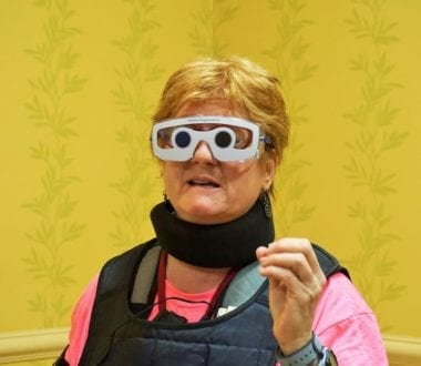Our Brain Health TMOM, Alli, learns what it's like to drive with cataracts while trying on the altered state suit that demonstrates aging. Photo by Yvonne Jasinski, Credit Card TMOM