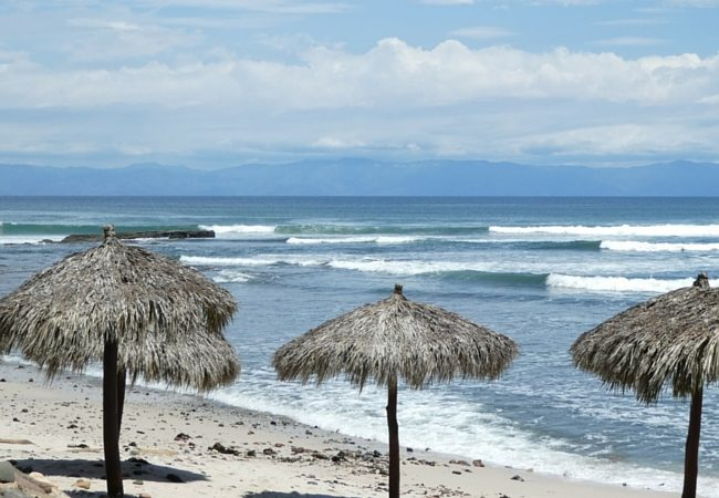 Thatched umbrellas line the beach along Banderas Bay at Royal Suites Punta de Mita.