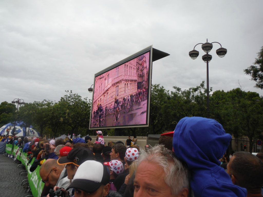 Find a place to stand where you can see both a giant screen and the Le Tour de France track allows you to experience the race first-person while also getting a gist of the final stage as a whole.