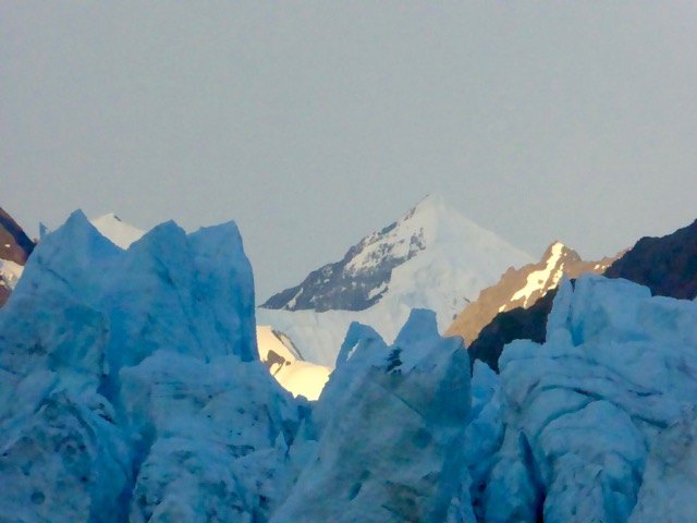 Glacial blue ice in foreground and mountain peak in background in Alaska's Denali National Park