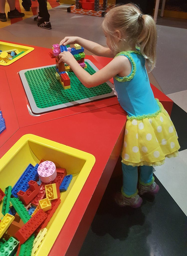 little girl playing with legos at a lego table Texas vacations for families