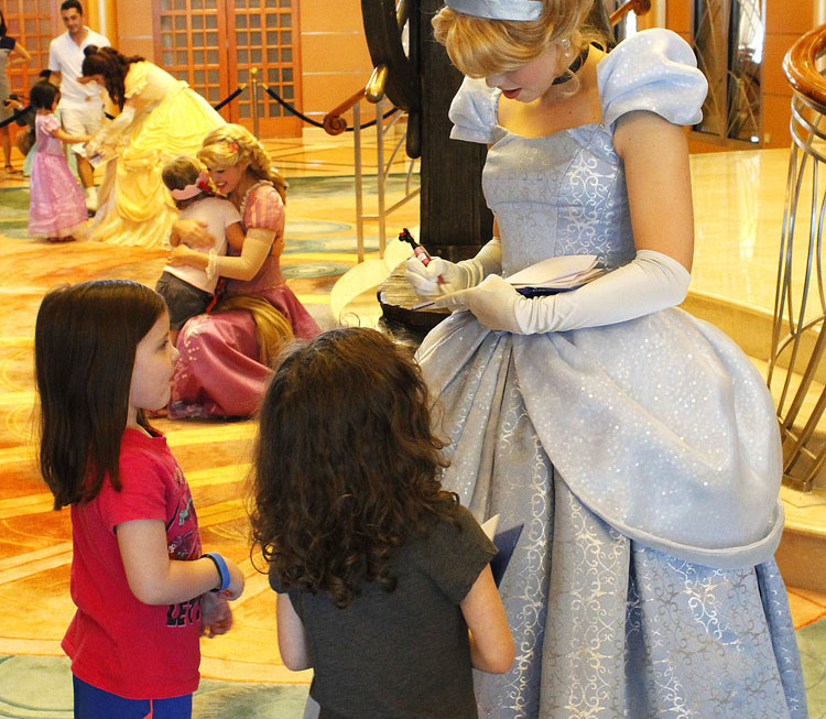 Cinderella signs autographs for her fans at her character meet.