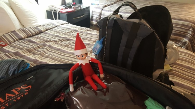 Traveling Elf on the Shelf enjoys a long nap in a suitcase.