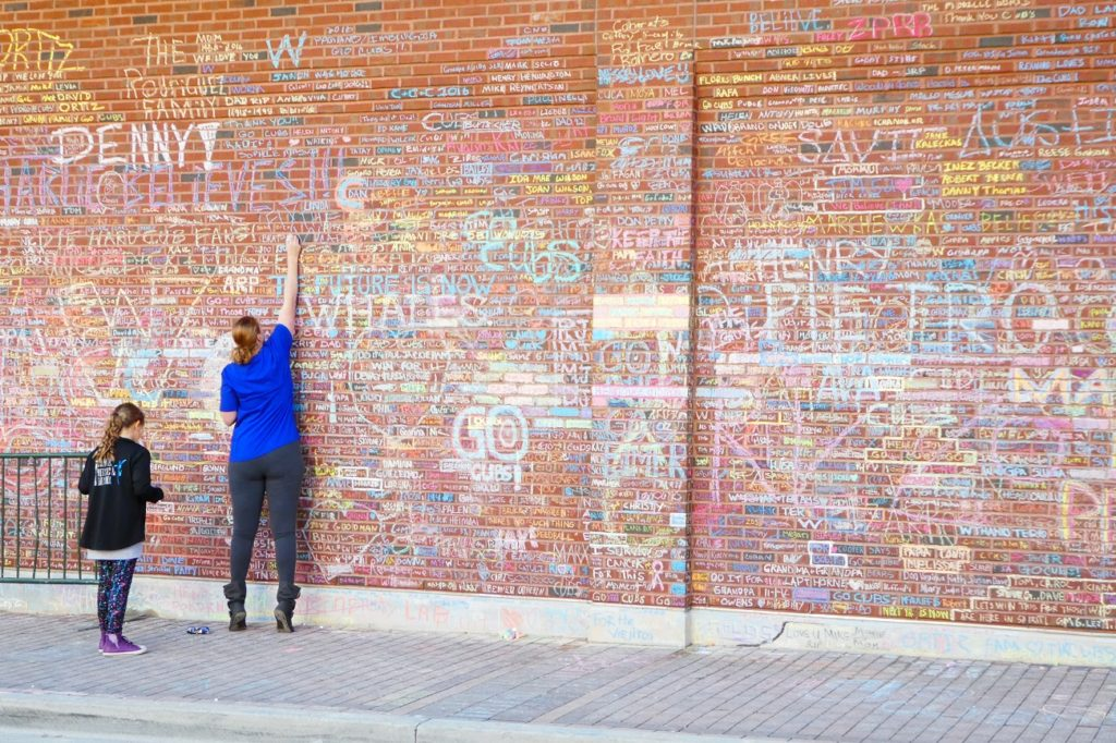 Photo by Jamie Bartosch/Suburban TravelingMom People using chalk to sign the walls of Wrigley Field after the Cubs' World Series win.