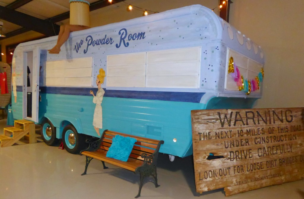 A vintage trailer is decked out as the campground's powder room complete with flamingo shower curtains and galvanized showers.