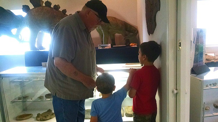 Earth Experience staff member talking to kids about coprolite, fossilized dinosaur poop