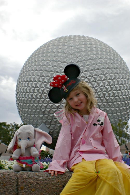 Young girl in Disney Mickey ears in front of Spaceship Earth before spending one day in Epcot.