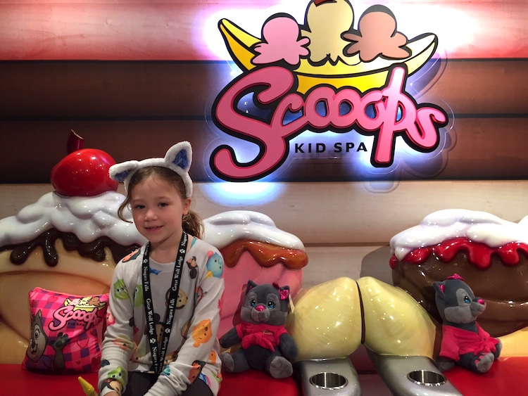 Young girl in front of Scoops Spa at Great Wolf Lodge Niagara