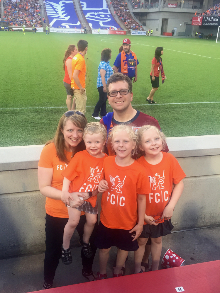 A family by the FC Cincinnati soccer field, celebrating spring in Cincinnati with the season opener