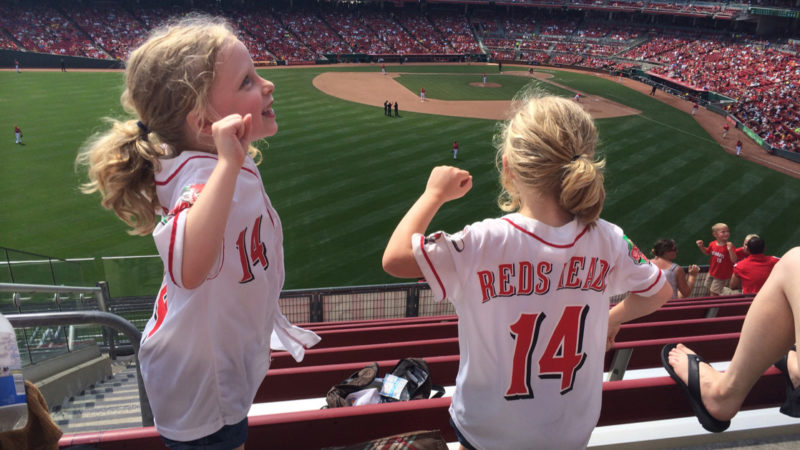 Two young girls cheer for the Cincinnati Reds at Great American Ballpark, where baseball is a must-do Spring activity for families