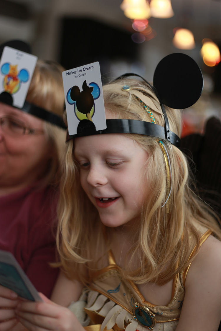 young girl playing headbanz (board game much like 20 questions, and a great option for road trips)