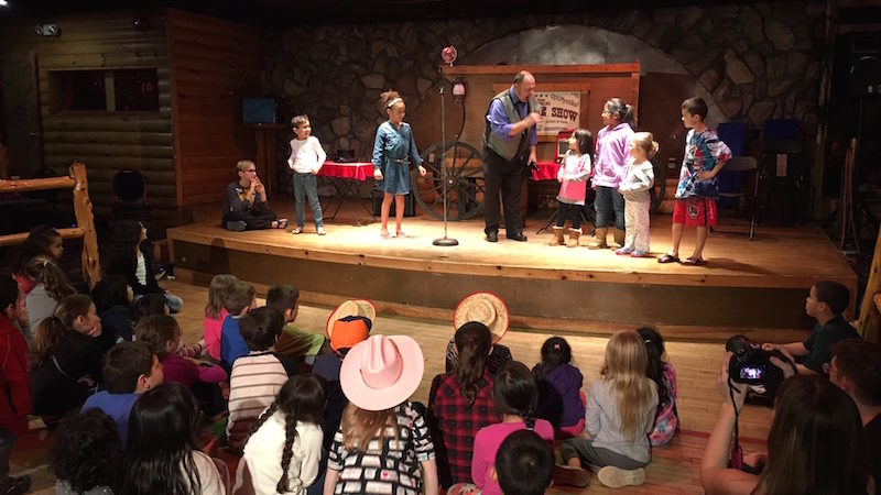 "An old-fashioned ""Medicine Man"" does magic for a live audience at Pinegrove Family Dude Ranch."