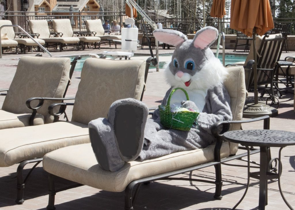 The Easter Bunny lounges by the pool before a hotel Easter egg hunt.