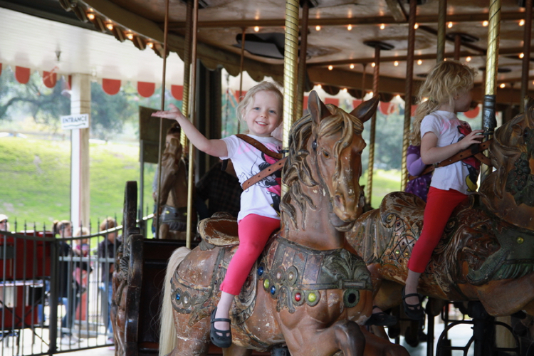 A young girl rides on a carousel in Griffith Park, Los Angeles, near Disneyland