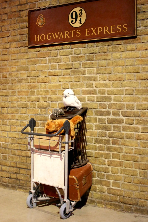 Push a cart through to platform 9 3/4 at the Harry Potter Studios Tour