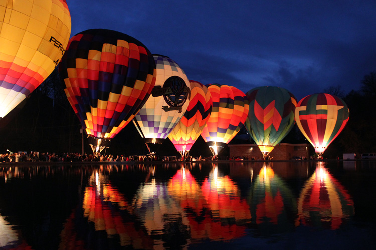 hot air balloons glow along Mirror Lake at Eden Park during Balluminaria, a free cincinnati activity held each fall