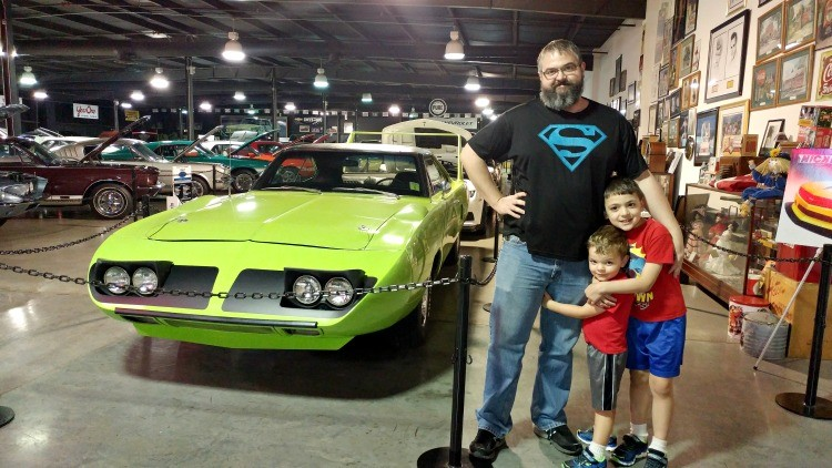 Dad and sons pose with the 69 Plymouth Roadrunner Superbee on display at the Floyd Garrett Muscle Car Museum in Sevierville, TN near Pigeon Forge; a visit makes a great gift for Father's Day in the Smokies.