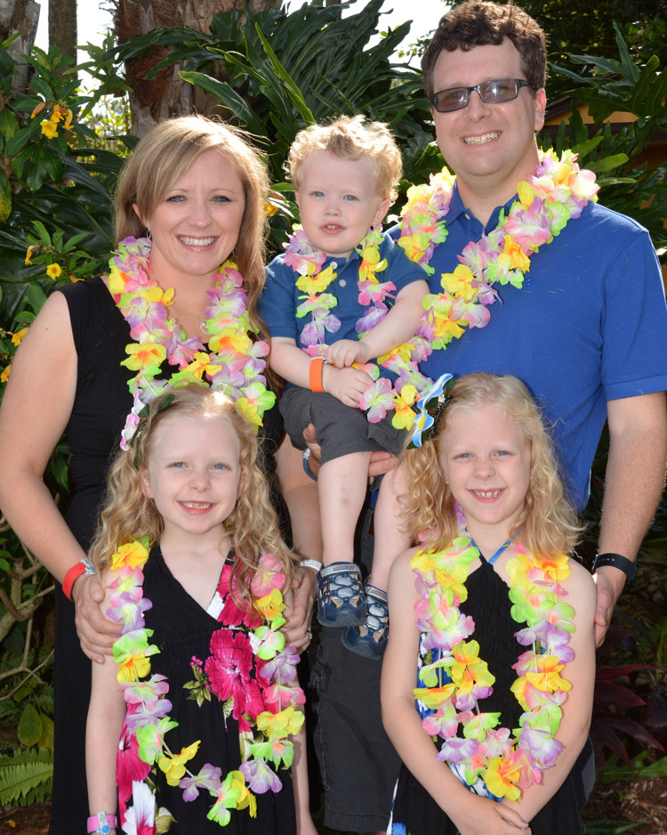 Family photos at Disney World with leis and a lush, beautiful background, taken at Disney's Polynesian Village resort
