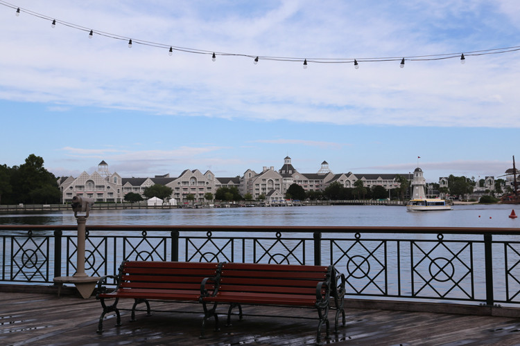 A bench on Disney's Boardwalk, with Crescent Lake and Disney's Yacht Club Resort in the background