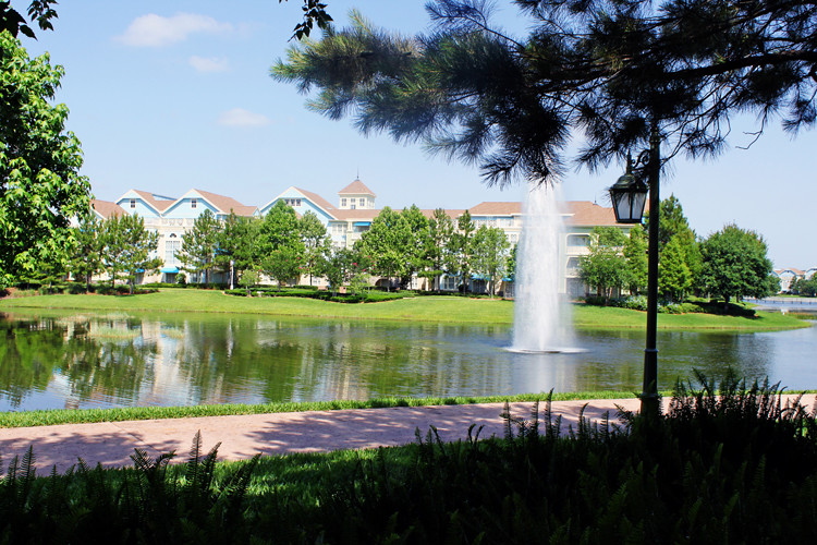Where to take family portraits? Lake, fountain, and foliage, with Disney's Saratoga Springs resort in the background