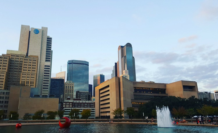 A photo of the Dallas, Texas downtown area with buildings and a fountain