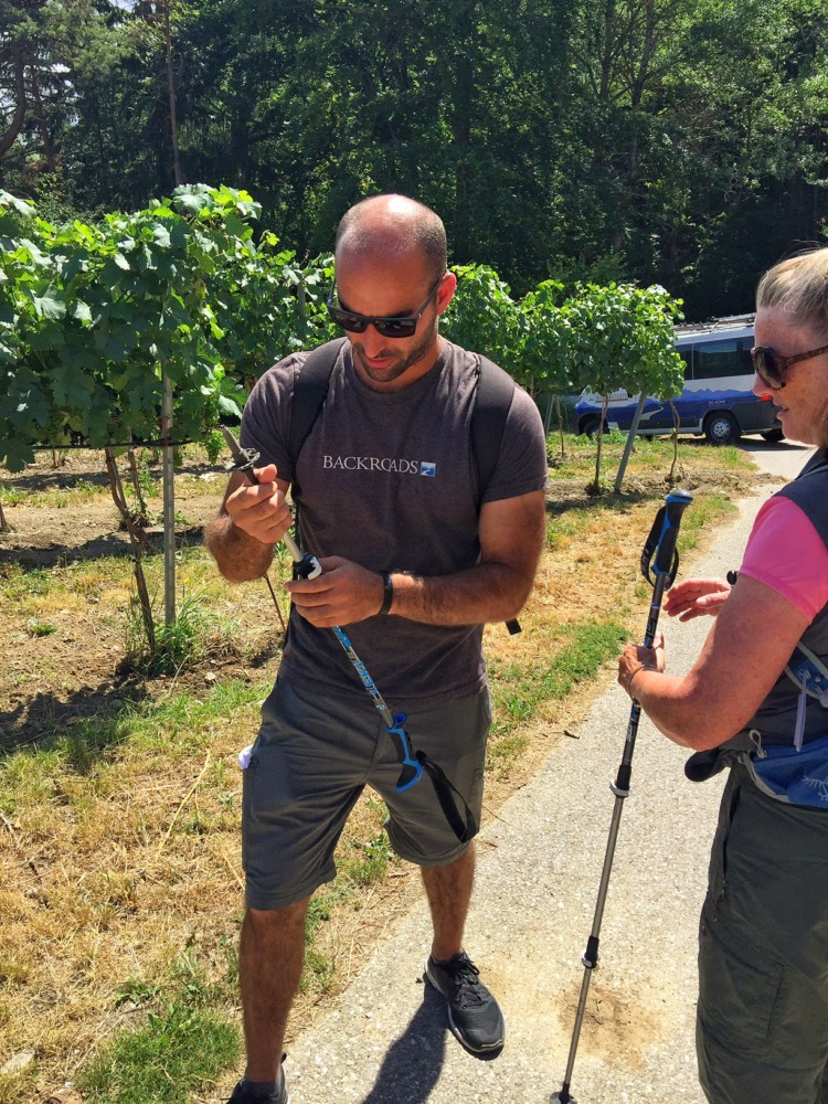 Backroads Travel guide fixes a walking stick for a travler hiking in Europe.