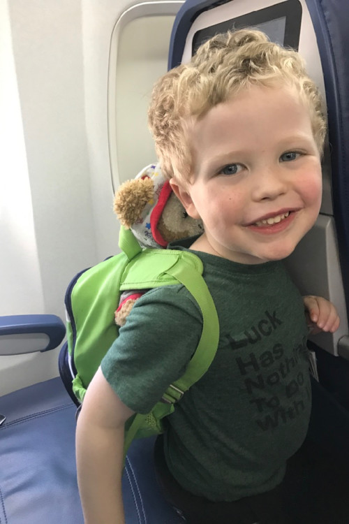 happy preschool boy carrying his own backpack with toys and snacks, another way to keep kids happy when traveling.