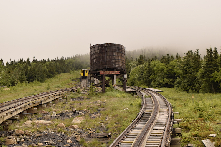 Mount Washington Cog Railway tracks climb into the clouds, a not to be missed New Hampshire road trip attraction.