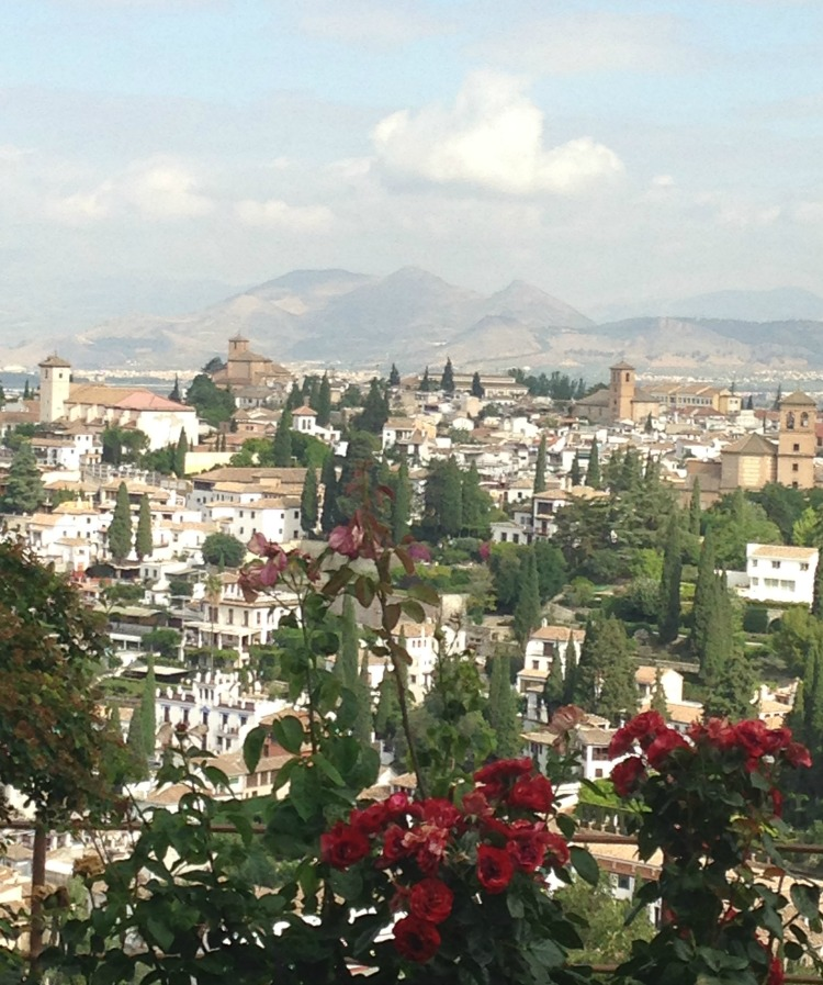 The magnificent Sierra Nevada mountains loom large in the background of the Spain city of Granada in the region of Andalusia.