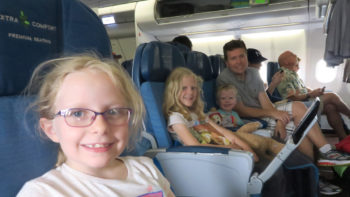 three school-age kids smiling on a plane, happy despite long travel days