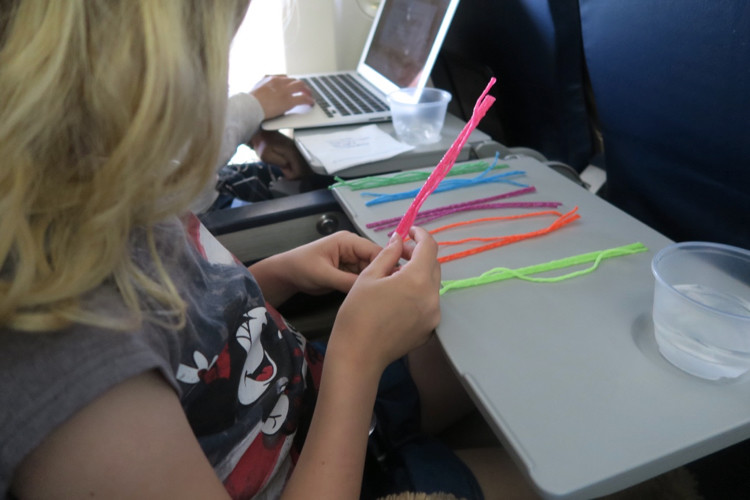 child playing with wikki stix on an airplane, 1 of many proven tips on how to keep kids happy when traveling.