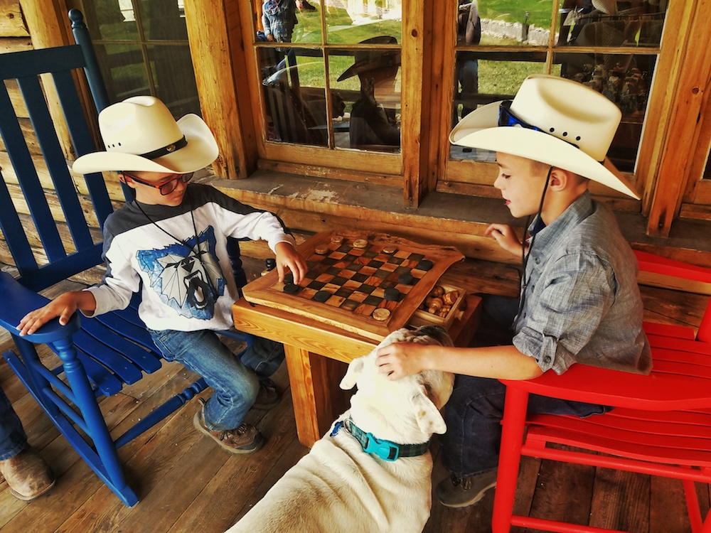 Kids can unwind on a dude ranch vacation by playing checkers on the porch of Rawah Guest Ranch.