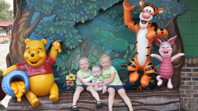 three kids pose with winnie the pooh, tigger, and piglet in a photo spot outside of the Walt Disney World parks