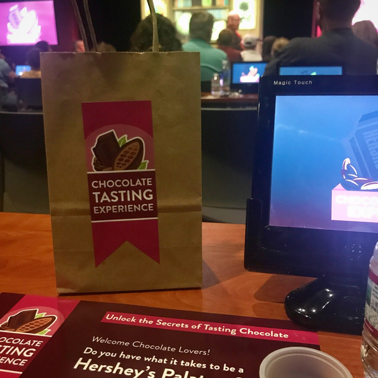 a brown bag of chocolate samples and interactive screen are part of the Chocolate Tasting Experience in Hershey's Chocolate World