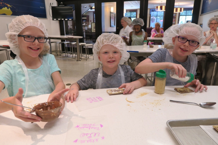 Three kids in hair covers and aprons work at a table making s'mores in the Chocolate Lab, 1 of 5 Attractions for Families in Hershey, Pennsylvania