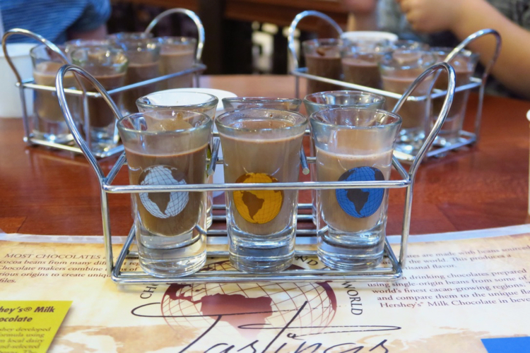 Several small glasses of liquid chocolate and a map of the world, given out at the chocolate tasting experience in the Hershey Story Museum., 1 of 5 Attractions for Families in Hershey, Pennsylvania