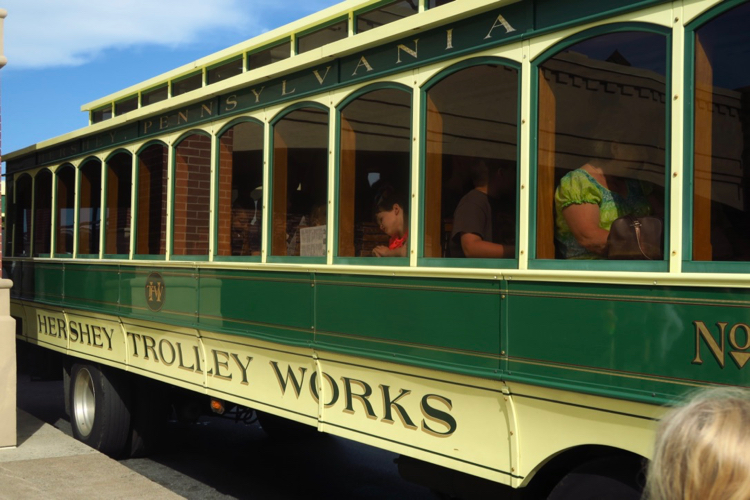 A green Trolley Works trolley with guests on board, before taking off on a kid-friendly seasonal tour around Hershey, Pennsylvania.